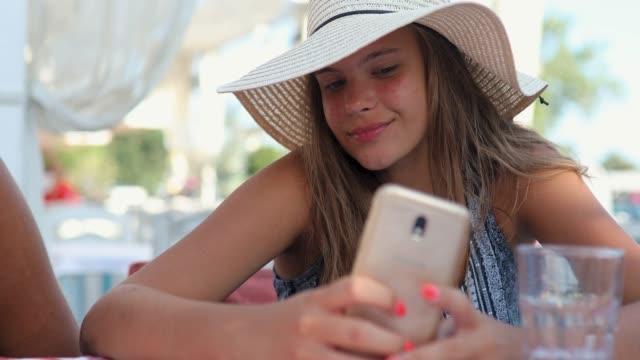 beautiful teenage girl taking selfie while sitting in restaurant on summer vacation with sun hat on - opalenizna filmów i materiałów b-roll