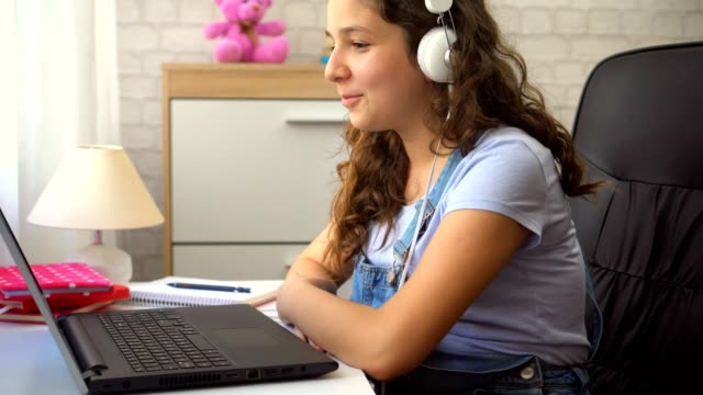 Beautiful Teenage Girl With Headphones Using a Laptop A Beautiful teenage girl with headphones using a laptop to finish her homework online learning stock videos & royalty-free footage