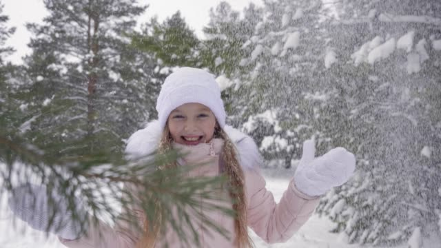 Beautiful teenager girl rejoicing winter snowfall in snowy forest slow motion