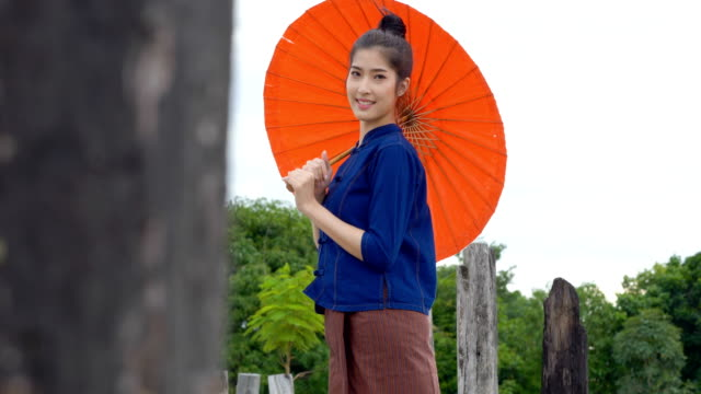 vídeos de stock e filmes b-roll de beautiful thai woman dressing with traditional style holding red umbrella in outdoor. - cultura tailandesa