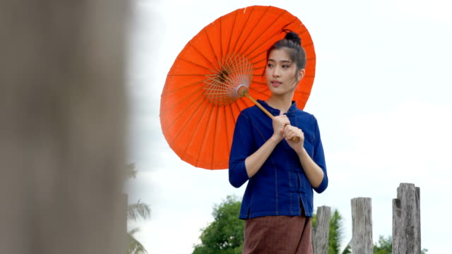 beautiful thai woman dressing with traditional style holding red umbrella in outdoor. - cultura tailandese video stock e b–roll