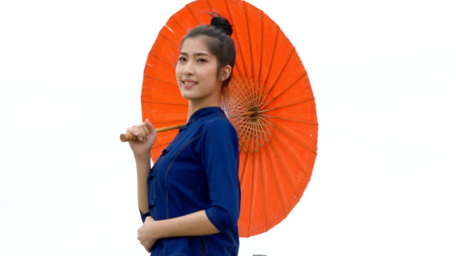 Beautiful Thai woman dressing with traditional style holding red umbrella in outdoor.