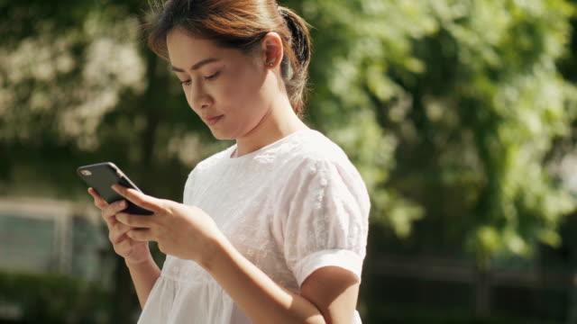 schöne thai frau nutzt smartphone im garten - urban gardening stock-videos und b-roll-filmmaterial