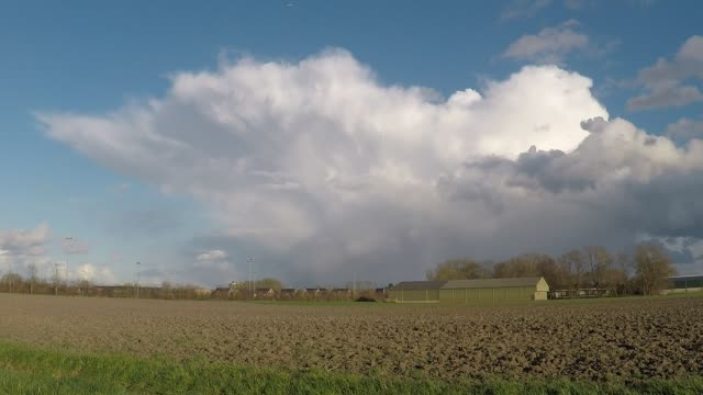 Beautiful time lapse of a thunderstorm moving over the dutch landscape Storm cloud with clear defined anvil is moving over the countryside of Holland. anvil stock videos & royalty-free footage