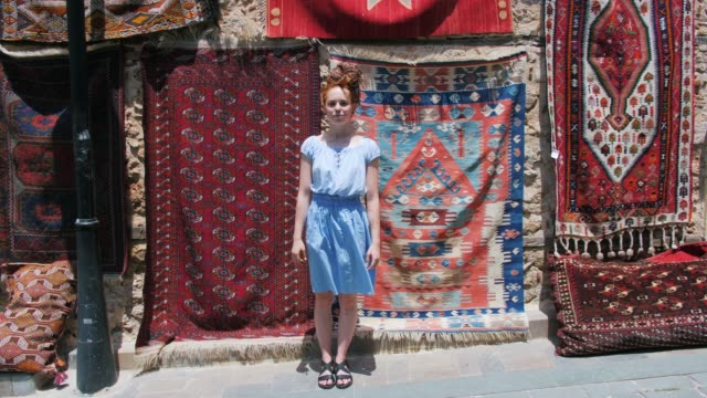 Beautiful tourist girl posing on street in front of old east oriental carpets