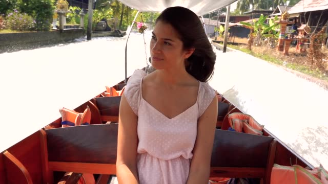 Beautiful tourist woman sightseeing from a boat in the floating market Damnoen Saduak in Ratchaburi, Thailand.