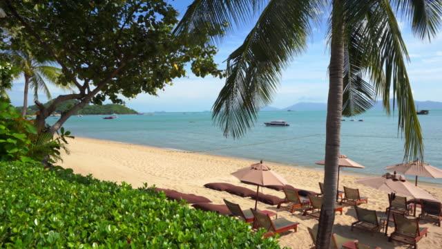schöner tropischer strand und meer mit sonnenschirm und stuhl lounge für urlaub und reisen - sun chair stock-videos und b-roll-filmmaterial