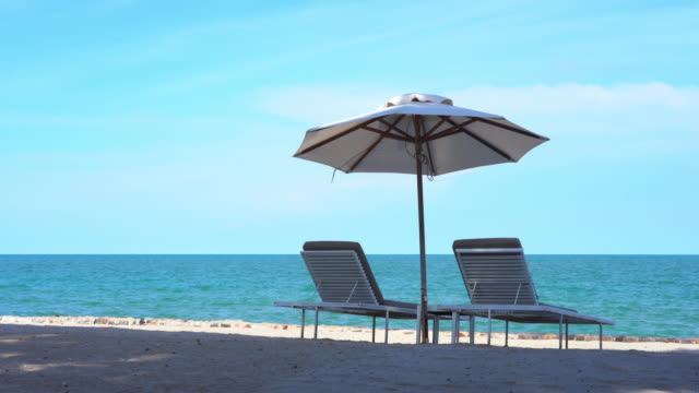 beautiful tropical beach and sea with umbrella and chair lounge for holiday and travel - albero tropicale video stock e b–roll