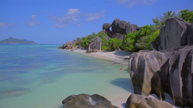 vídeos de stock, filmes e b-roll de bela praia tropical anse source d ́argent com rochas esculpidas de granito e palmeiras - ilha de la digue, seychelles, ilhas do oceano índico. - penedo