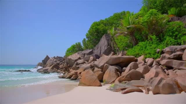 vídeos de stock, filmes e b-roll de praia tropical bonita petite anse com rochas e palmeiras sculpted do granito - console de la digue, seychelles, consoles do oceano índico. - penedo