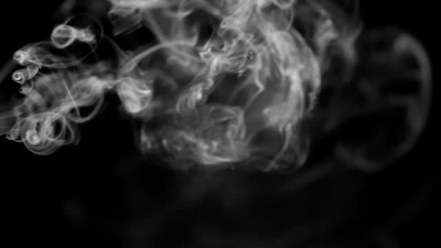 Beautiful twists of white smoke on a black background video