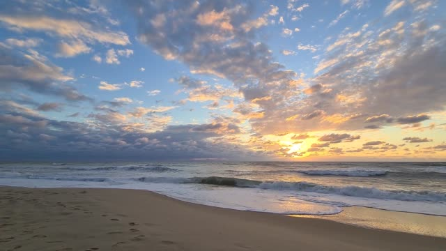Beautiful video clip of a cloudy sunset at the ocean beach Beautiful video clip of a cloudy sunset at the ocean beach in Lacanau Ocean in France, Europe. coastal feature stock videos & royalty-free footage