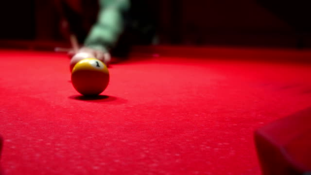 Beautiful view of a professional billiard player, puts ball N1 in the hole. video