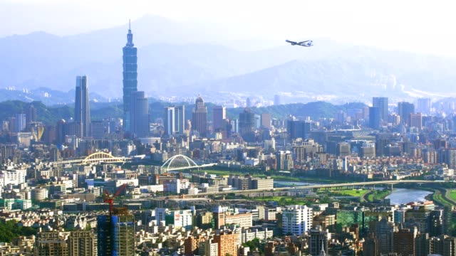 Beautiful view of an airplane flying over Taipei city at sunset video