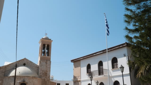 Beautiful view of greek flag on high flagpole flying in the air with church on background