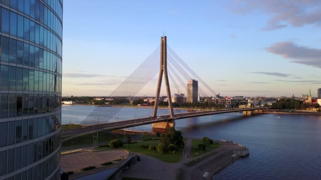 beautiful view of the riga city bridge by the nearest skyscraper - латвия стоковые видео и кадры b-roll