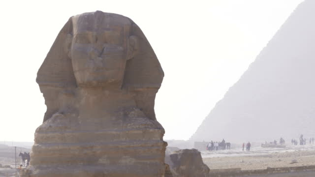 beautiful view of the sphinx  in egypt. we can see clouds in the sky above the unesco classified monument, with pyramids in the background. - ancient architecture stock videos & royalty-free footage
