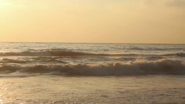 vacker utsikt över vågorna och fiskebåtarna längs marina stranden under soluppgången, chennai, indien. fiskare som beger sig ut i havet tidigt på morgonen. - indiska oceanen bildbanksvideor och videomaterial från bakom kulisserna