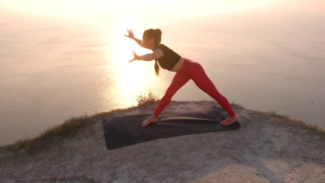 Beautiful view of woman doing yoga One-Legged Downward-Facing Dog Pose, High Lunch Pose on the mountain with sea view at sunset. video