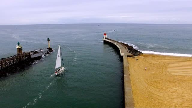 大西洋につながる堤防の美しい眺め。堤防の間の海へ出港ヨット。 - 大西洋点の映像素材/bロール