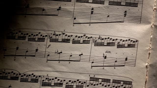 vidéos et rushes de notes de musique vintage, vent ups pages, peu de lumière, gros plan - compositeur
