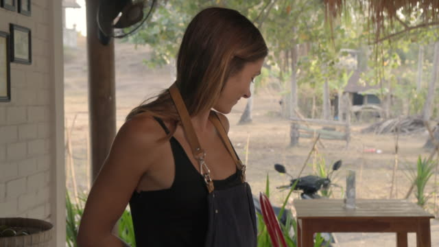 vídeos de stock e filmes b-roll de beautiful waitress putting on apron and preparing outdoor restaurant for guests - avental