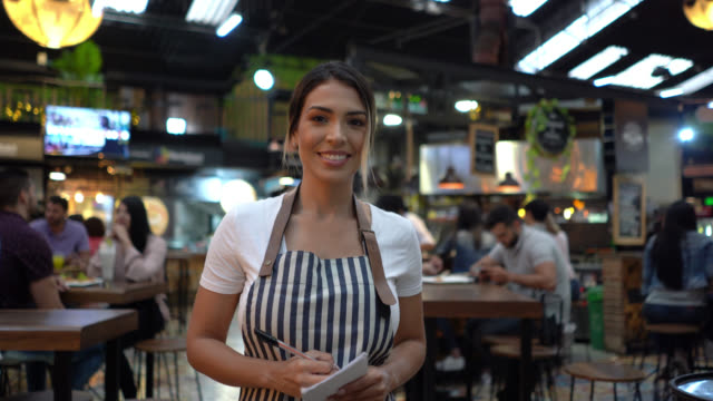 vídeos de stock e filmes b-roll de beautiful waitress writing an order on notepad and then smiling at camera - avental