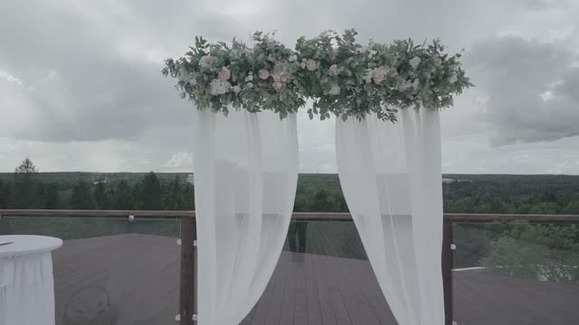 A beautiful wedding arch is located on the roof of a tall building. A natural landscape is visible in the background