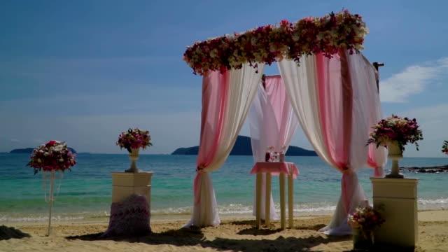 Hermosa boda arco con flores en la playa. - vídeo