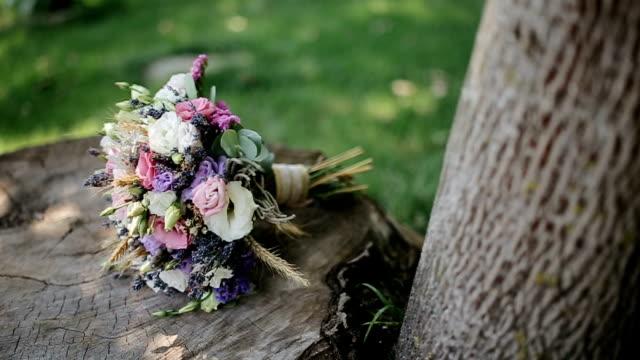 bellissimo bouquet di nozze sdraiato su un albero di ceppo - bouquet video stock e b–roll