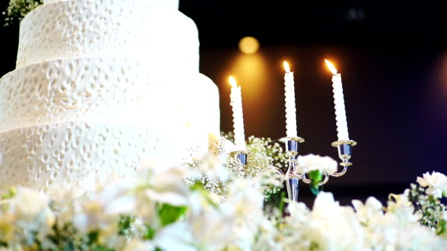 Beautiful wedding cake decorated with flowers and candles at wedding reception. video