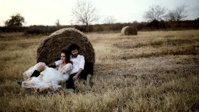 Beautiful wedding couple sitting in the meadow