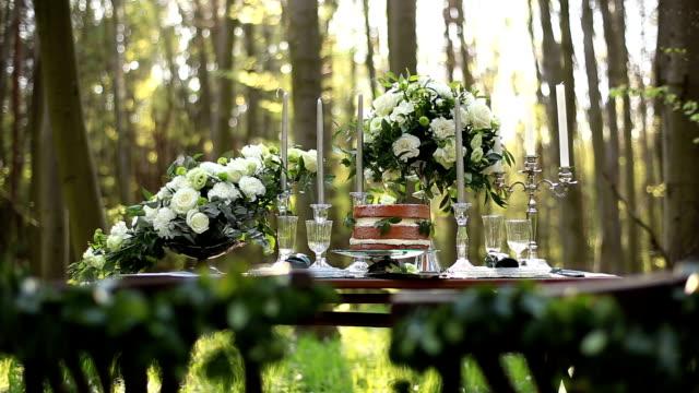 vídeos de stock, filmes e b-roll de bela mesa decorada para casamento atribuido para dois na natureza na floresta. decoração de casamento com buquê de rosas brancas e vintage candelabro perto do bolo de chocolate - rústico