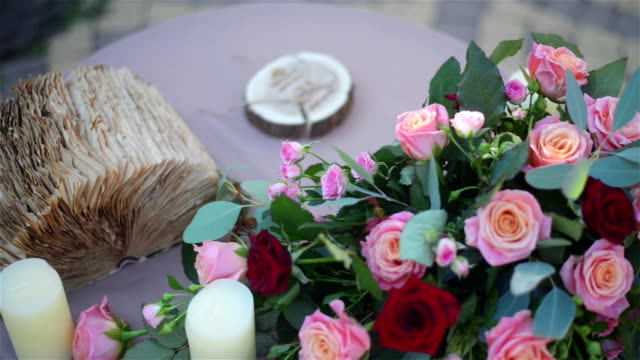 Beautiful wedding decorated table setted for two on nature in the garden. Wedding decoration in violet and red colors. Flowers, candles and decorative old book. Slow pan. video