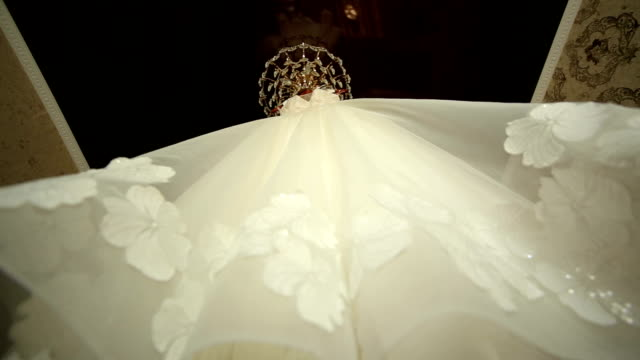 Beautiful wedding dress hung on the chandelier. video