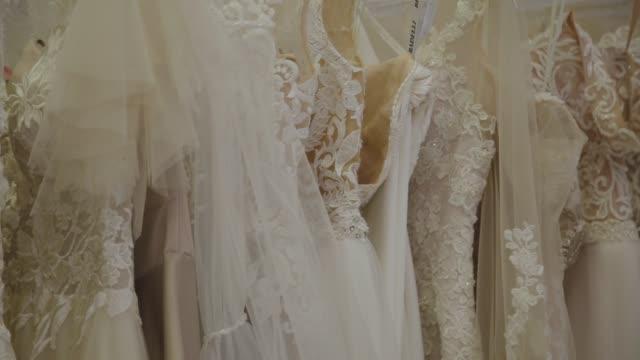 Beautiful wedding dresses in a bridal salon Beautiful wedding dresses in a bridal salon coathanger stock videos & royalty-free footage