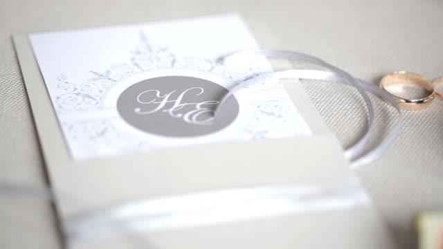Hermosa invitación, anillos, cintas, atmósfera de celebración de la boda - vídeo