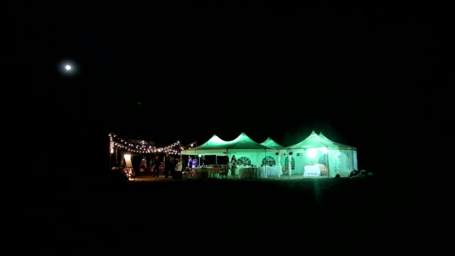 Beautiful wedding tent set up for an outdoor reception. This is a long night exposure, there is blur under the tent showing activity video