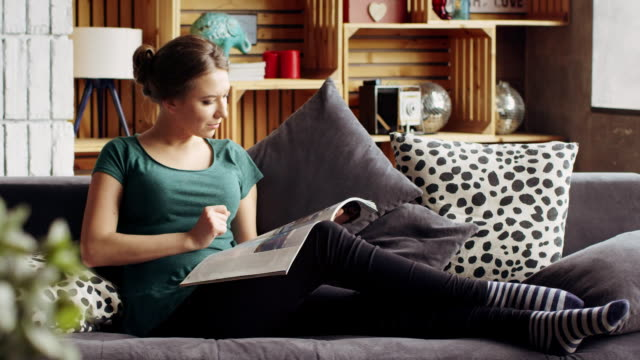 Beautiful well-groomed woman reading a fashion magazine lying on the sofa in the living room