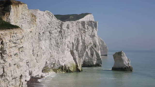 Beautiful white chalk cliff stack Seaford East Sussex England UK near Seven Sisters with waves lapping video