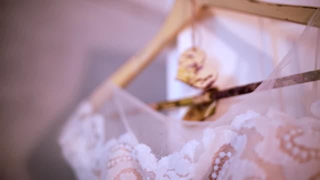 Vestido de novia blanco hermoso está colgando de una percha en un dormitorio. Preparación de la novia s mañana, detalle en estilo rústico - vídeo