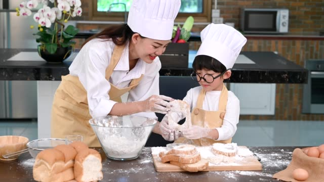 beautiful woman and cute little asian boy with eyeglasses, chef hat and apron playing and baking bakery in home kitchen funny. homemade food and bread. education and learning concept. thai person - formare pane video stock e b–roll