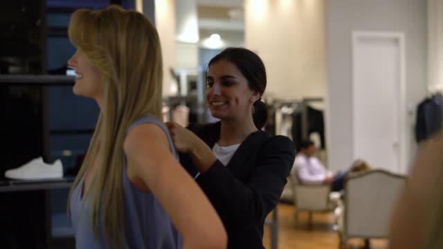 美しい女性と彼女は測定中に誰かに話してセールスレディ - 小売販売員点の映像素材/bロール