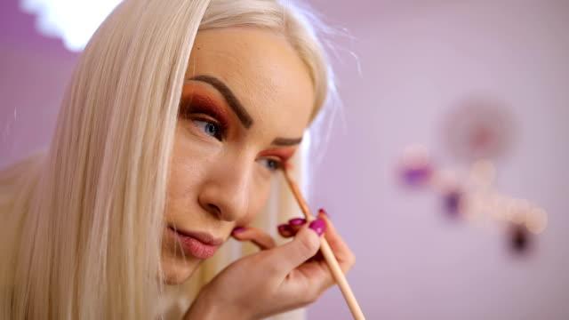 Beautiful woman applying make up on eyes