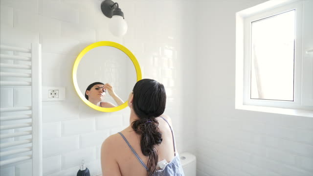 vídeos de stock e filmes b-roll de beautiful woman applying mascara in bathroom. - rímel