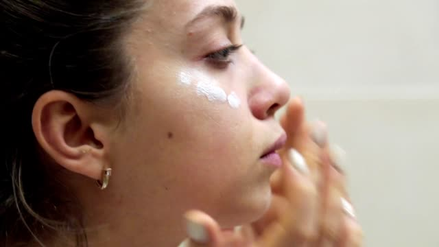beautiful woman applying skincare lotion to face caring for skin with feminine beauty products - sun cream stock videos & royalty-free footage
