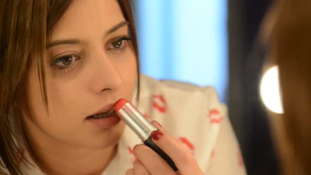 Beautiful woman applyling lipstick Close-up of beautiful white caucasian female fashion model applying lipstick. lip liner stock videos & royalty-free footage