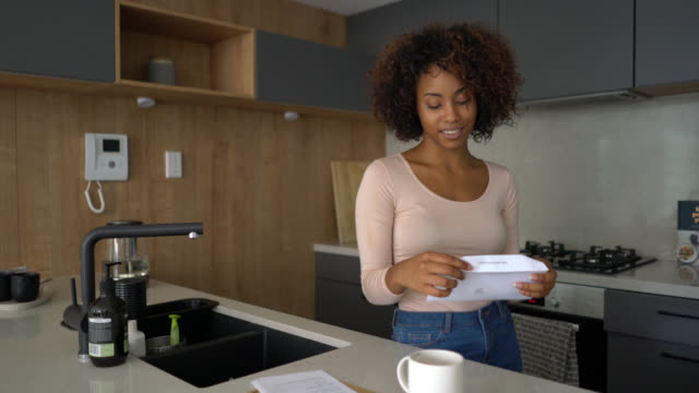 Beautiful woman at home checking her mail opening an envelope