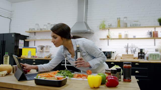 vidéos et rushes de belle femme à la maison cuisinant un repas délicieux suivant une recette en ligne sur la tablette - recette