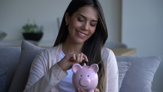Beautiful woman at home putting coins into her piggy bank while sitting on couch very happy Beautiful woman at home putting coins into her piggy bank while sitting on couch very happy and smiling piggy bank stock videos & royalty-free footage